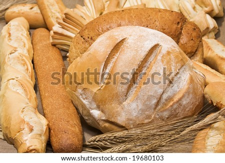 Bread assortment with country bread in the center. Country bread on focus. - stock photo