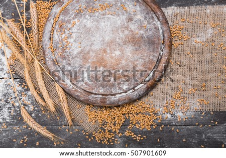 Bread baking background. Grain and ears scattered around on rustic wood near round wooden desk sprincled with flour. Agricultural wheat harvest, bread making composition