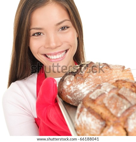 Bread baking woman showing loaf of bread fresh from oven. - stock photo