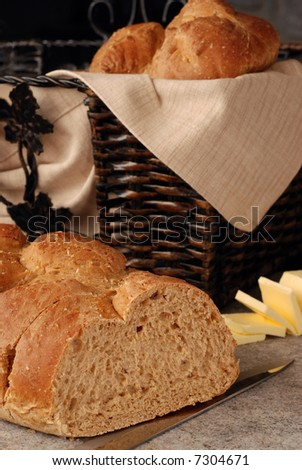 Bread Basket still-life.  Freshly baked, 9-grain, Italian bread on a ceramic cutting board with knife.  Basket of bread and sliced butter in soft focus in the background. - stock photo