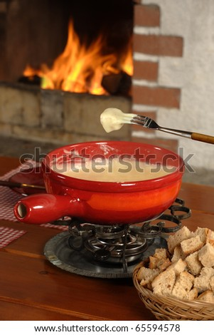 Bread being dipped into the melted cheese in the fondue bowl. - stock photo