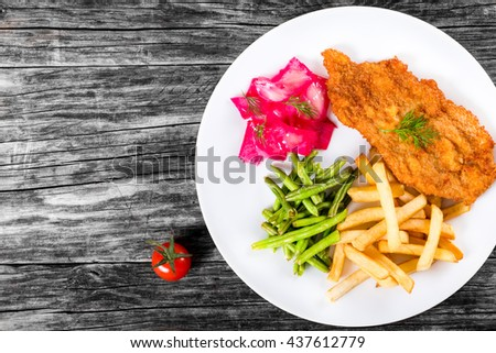 bread crumb coated fried pork chop with french fries, green bean and salad with dill and cabbage marinated in red wine vinegar and beet juice, close-up, view from above