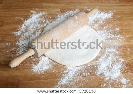 bread dough on wooden kitchen counter with rolling pin - stock photo