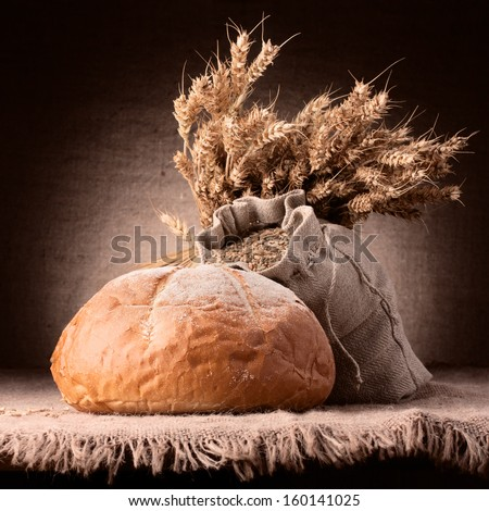 Bread, flour sack and ears bunch still life on rustic background - stock photo