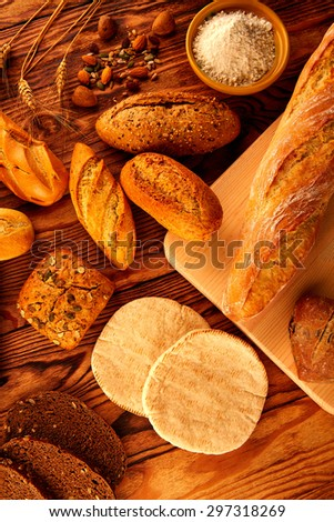 Bread fresh varied mix on golden rustic wood golden table - stock photo