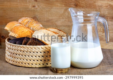 Bread from rye and wheat flour of rough grinding and glass of fresh cow's milk - stock photo