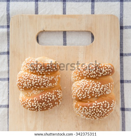 Bread hotdog with sesame on wood background. - stock photo
