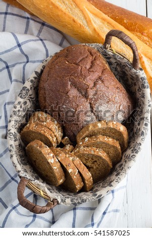 Bread in a basket, a baguette on a wooden background