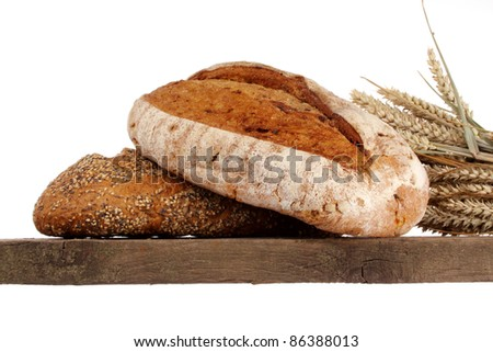 Bread loaf, buns and rolls in a studio setting against white background - stock photo