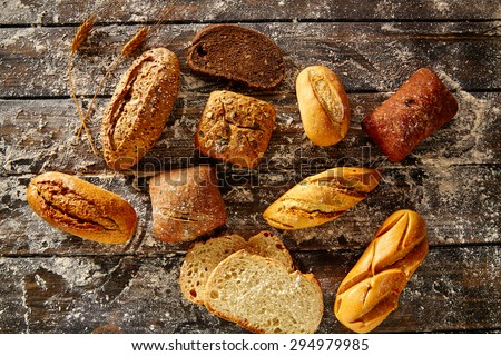 Bread loaf mixed in a rustic wood and wheat flour aerial view - stock photo