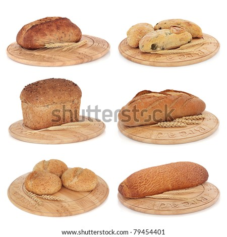 Bread loaf selection of rye, brown, tiger, wholegrain, with olive and granary rolls each on a carved bread board with wheat sheaths, isolated over white background.