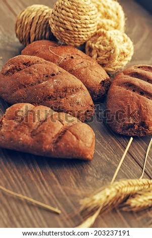 Bread loaves and balls made of rope on wood