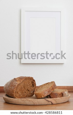 Bread on table, empty picture frame on wall, in background, stock picture - stock photo
