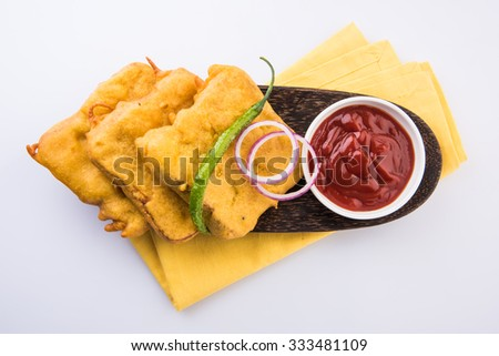 Bread Pakora or bread pakoda served along with tomato ketchup green chilly and onion slices, indian snack, served on wooden plate with yellow napkin, isolated top view on white background