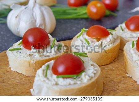 bread pieces with vegetable spread, chive and tomatoes