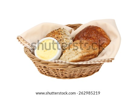 Bread rolls with butter in a wicker basket with a serviette isolated against white - stock photo