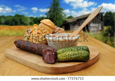 Bread, smoked cheese, kielbasa and other traditional food served outside in the countryside
