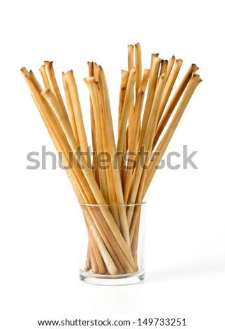 bread sticks in a glass over white - stock photo