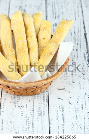 Bread sticks  in wicker basket on wooden background - stock photo