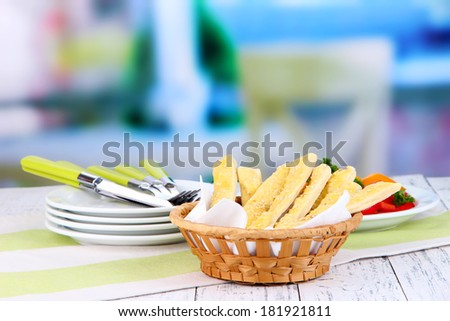 Bread sticks  in wicker basket on wooden table on light background - stock photo