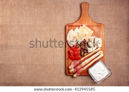 Bread sticks with prosciutto Cured Meat on a wooden cutting board with pita bread, red tomatoes, olives, cheese and other ingredients for a lunch snack - stock photo