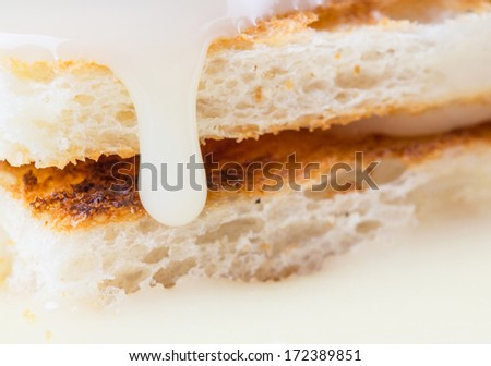 Bread toast and drips of condensed milk close up view - stock photo