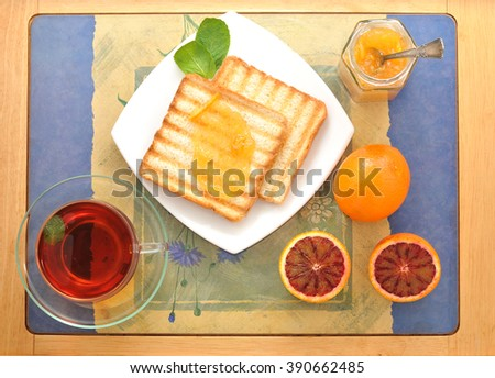 bread toast with orange marmalade. black mint tea in a transparent mug and blood oranges on a tray. Breakfast in the morning. top view - stock photo