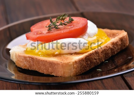 Bread toasted with poached egg and tomato slice, close up view - stock photo