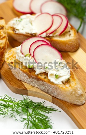 Bread Toasts with White Cheese and Radishes. Selective focus. - stock photo