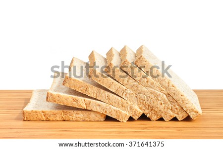 Bread, whole wheat slice on wooden table isolated in white background - stock photo
