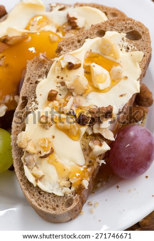 bread with butter, honey, nuts and grapes, vertical, close-up, top view - stock photo
