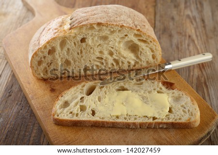 Bread with butter on a rustic cutting board - stock photo