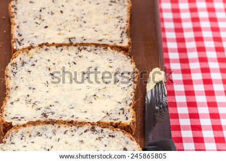 bread with butter on wooden board  - stock photo