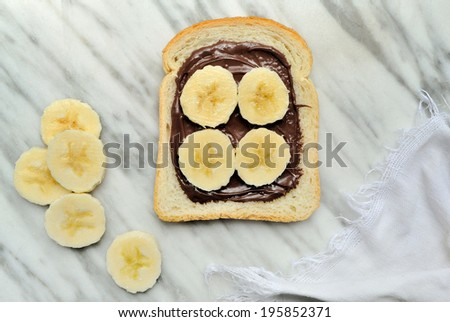 Bread with chocolate cream and slices of banana - stock photo