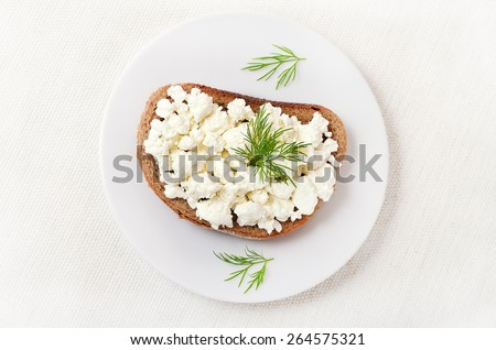 Bread with curd cheese and dill on white plate, top view - stock photo