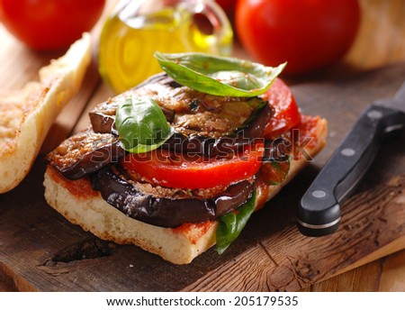 bread with eggplant and tomato on wooden table