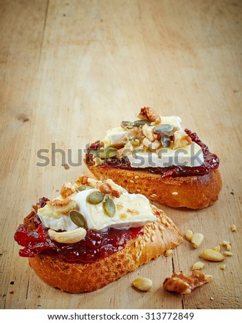 bread with jam and brie cheese on wooden table