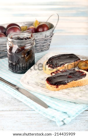 Bread with plum jam and plums on wooden table