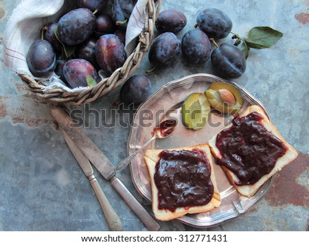 Bread with plum jam on silver plate with rustic cutlery - stock photo