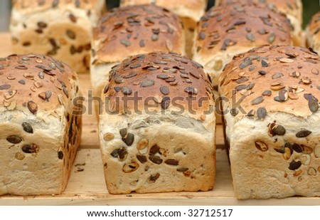 Bread with pumpkin seeds lay on the table. - stock photo