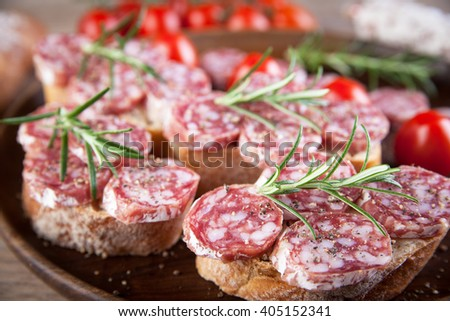 Bread with sliced salami served on a plate - stock photo