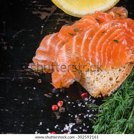 Bread with sliced salted salmon, served on black wooden table with lemon, sea salt and peppers. Square image with selective focus - stock photo
