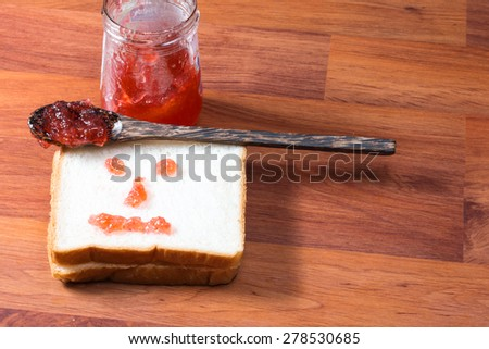 Bread with strawberry jam on wooden table - stock photo