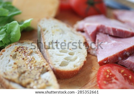 Bread with whole-grain mustard, ham slices, cheese, lettuce and tomato, ready to make into a lunch sandwich - stock photo