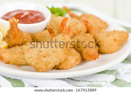 Breaded Butterfly Prawns - Deep fried battered prawns filled with garlic sauce served with chili sauce and lemon wedges.