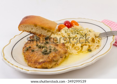 Breaded chicken baked to a golden brown in lemon garlic butter sauce and topped with capers.  Served with pasta garnished with parsley.  Horizontal on white background with copy space. - stock photo