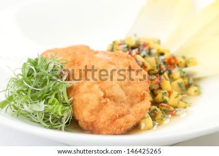 Breaded chicken chop with mango salsa - stock photo