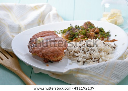 Breaded chicken fillet with rice and mushrooms as a garnish. - stock photo