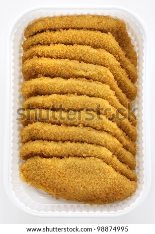 breaded chicken fillets in a plastic box, ready for a meat market - stock photo