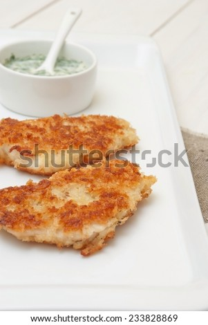 Breaded fish fillet with yogurt dip - stock photo